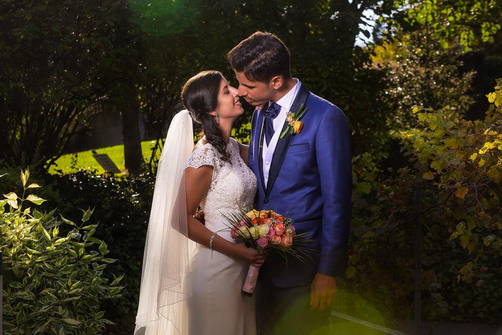 baiser volé de mariés juste après s'être dit OUI. photo dans un parc avec des flares