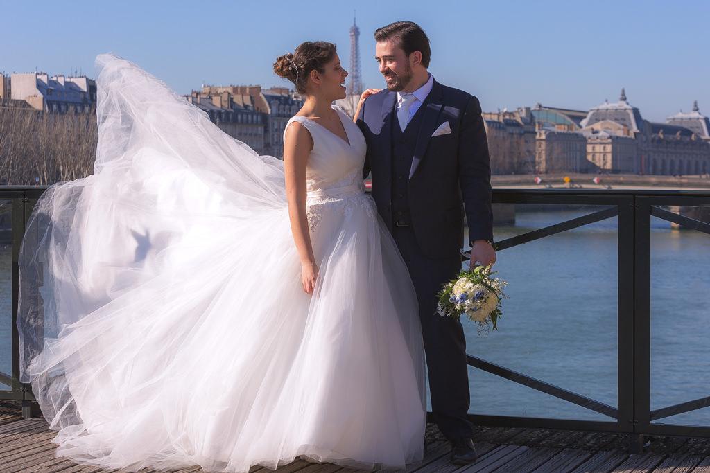 mariés sur le pont des arts avec la tour eiffel et robe qui vole
