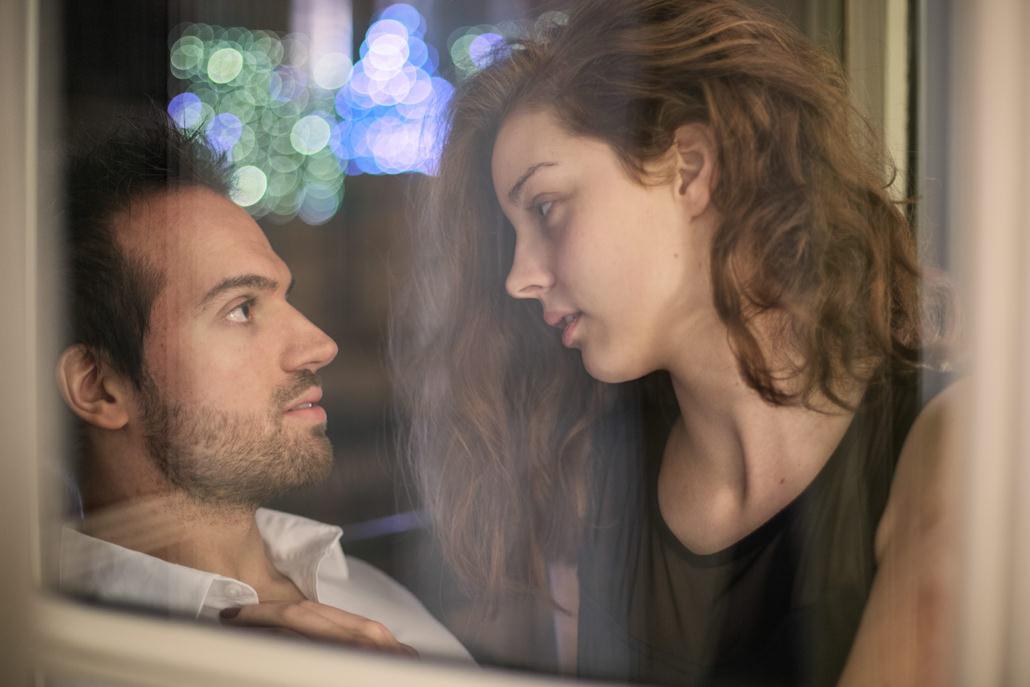 couple se regarde dans le reflet de la fenêtre
