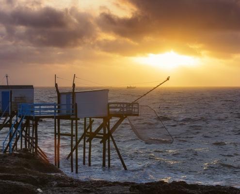 Carrelets et bateau sous coucher de soleil dans les nuages