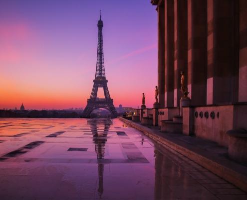 tour eiffel et trocadéro vide, reflet dans une flaque d'eau et ciel très rosé du matin
