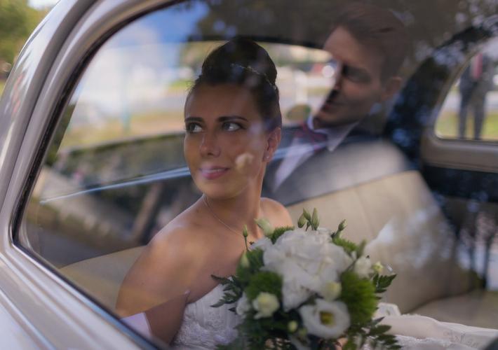 mariée dans une voiture qui regarde son mari qu'on voit dans le reflet de la vitre