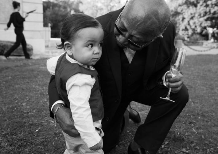 petit garçon avec son grand père qui louche sur une coupe de champagne