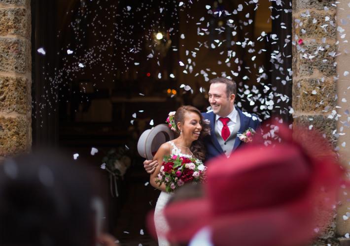couple qui sortent de leur cérémonie religieuse, jeté de riz et de pétales de roses
