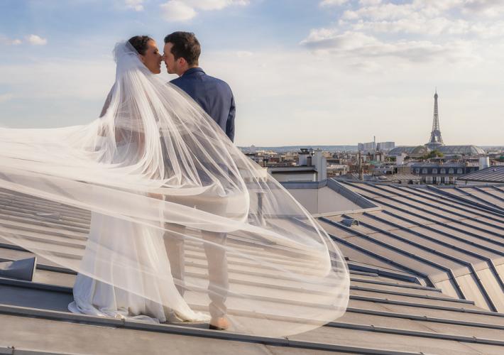 couple de mariés sur un toit avec tour eiffel et voile volant