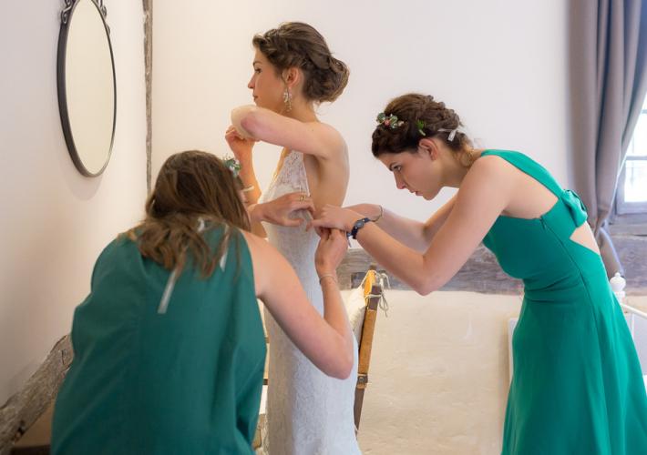 mariée qui se prépare avec ses témoins et meilleures amies devant le miroir