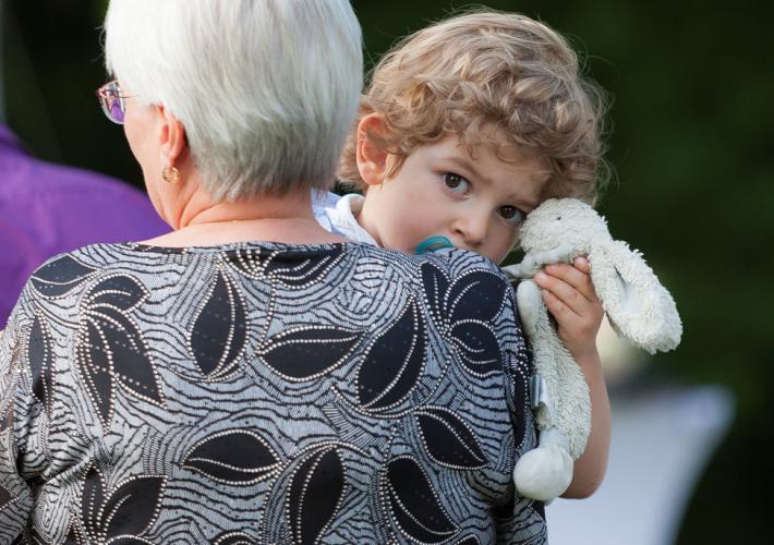 enfant fatigué dans les bras de sa grand mère
