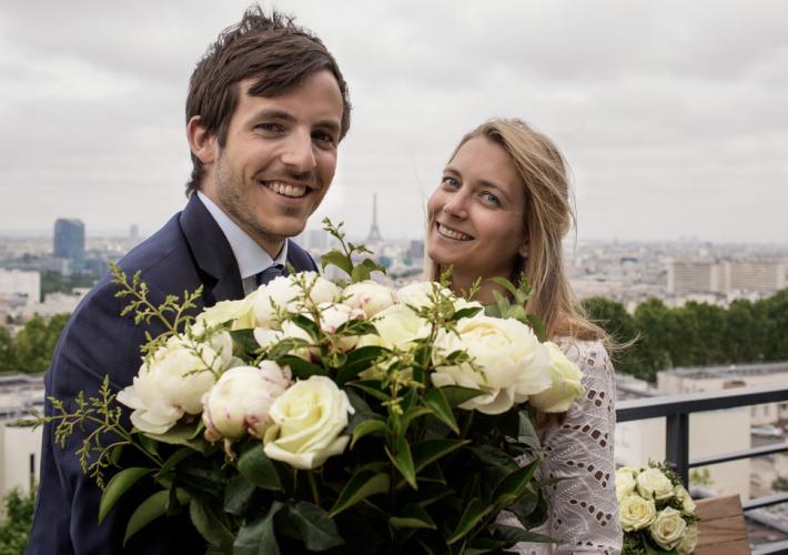 mariés avec fleurs et au milieu la tour eiffel